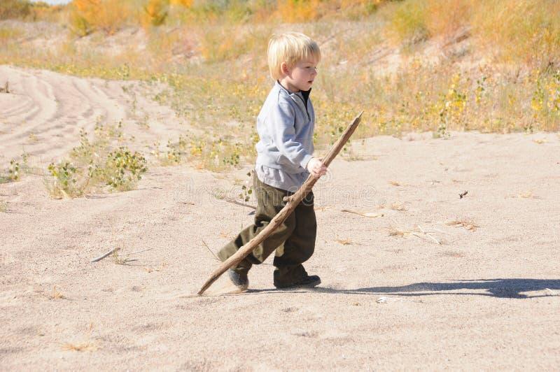 Jongen die op zandduinen loopt stock foto's