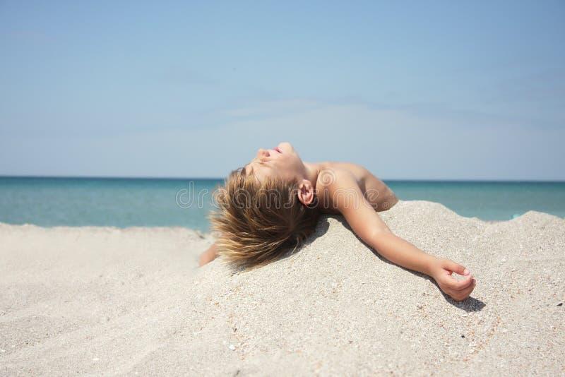Jongen die op zandstrand rust op hete zonnige dag stock foto