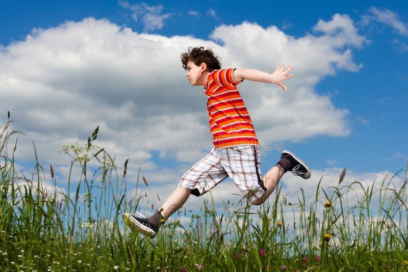 Jongen die, openlucht springen loopt stock foto