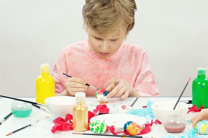 Jongen die Paasei schildert stock afbeelding