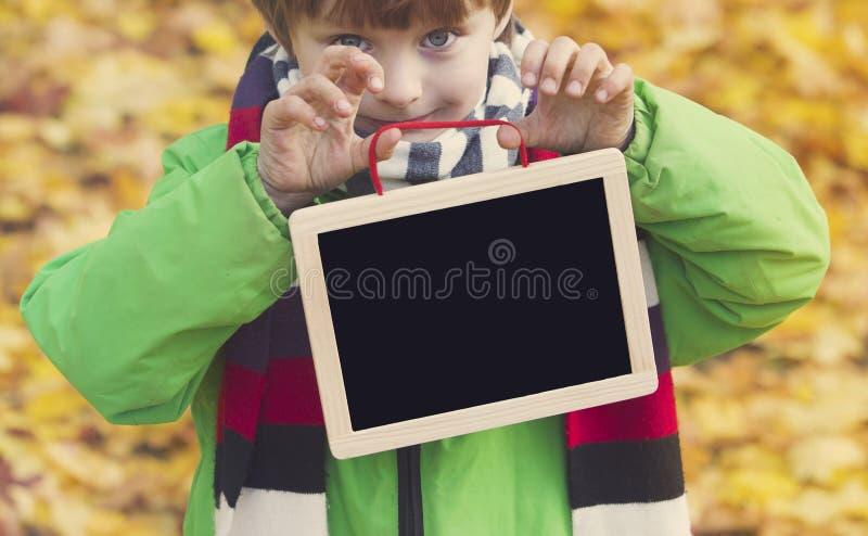 Jongen die in park een bord houden stock foto's
