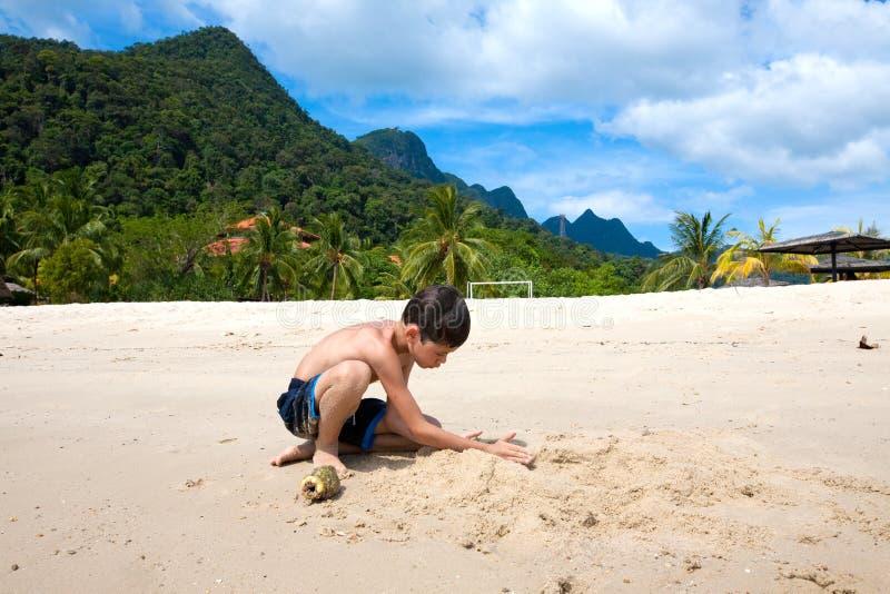 Jongen die pret hebben die in openlucht in het zand door het strand in tropisch eiland spelen stock foto's