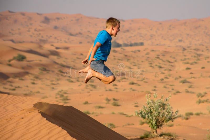 Jongen die pret heeft die van oranje zandduinen springt met een eindeloos zand in achtergrond en reusachtige luchttijd stock foto's