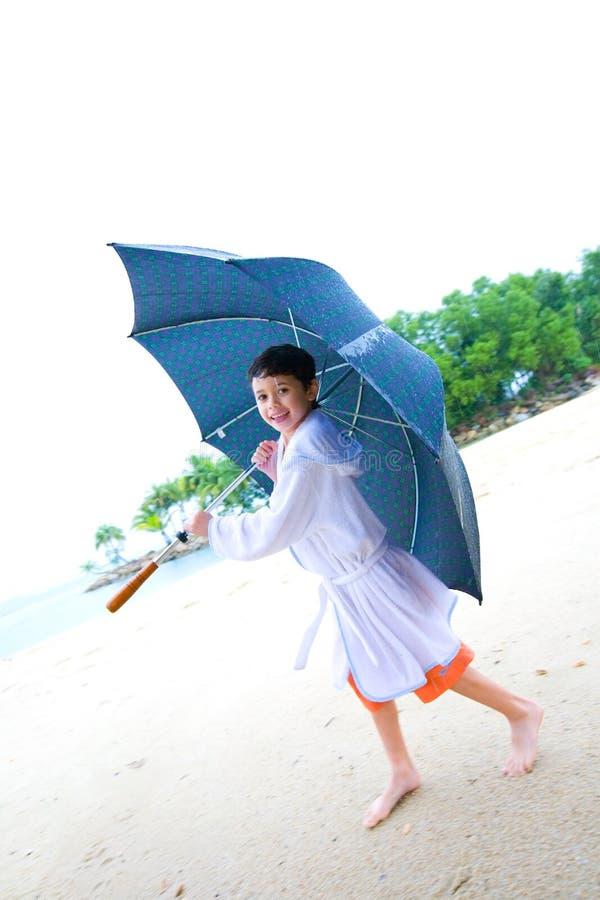 Jongen die pret met grote paraplu heeft bij het strand royalty-vrije stock foto