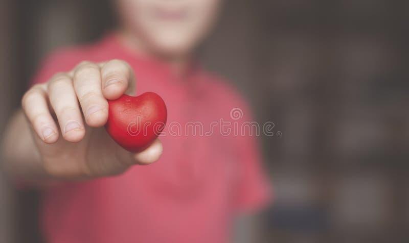 Jongen die rode hartvorm houden stock afbeeldingen