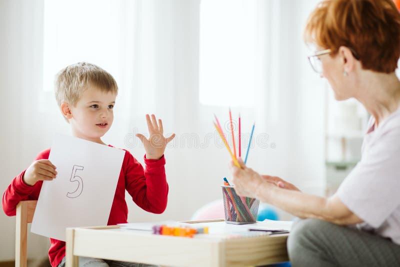 Jongen die in rode sweater tijdens buitenschoolse activiteiten leren te tellen stock afbeelding