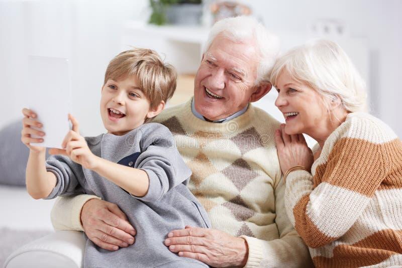 Jongen die selfie met grootouders nemen royalty-vrije stock fotografie