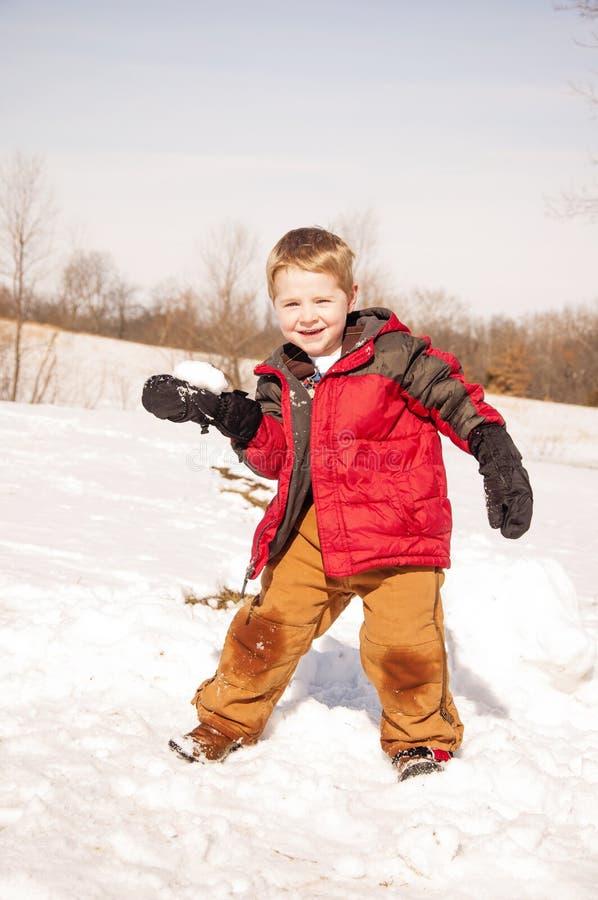 Jongen die sneeuwbal werpen stock afbeeldingen