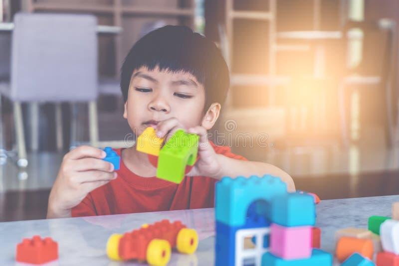 Jongen die Stuk speelgoed blokken op een woonkamer voor onderwijsstuk speelgoed stapelen stock foto