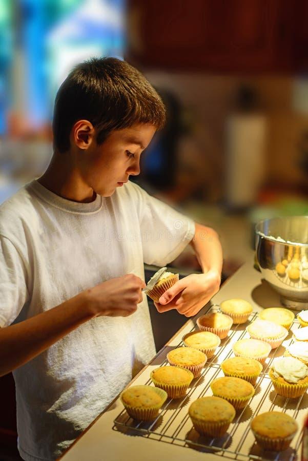 Jongen die Suikerglazuur op Cupcakes zetten stock foto's