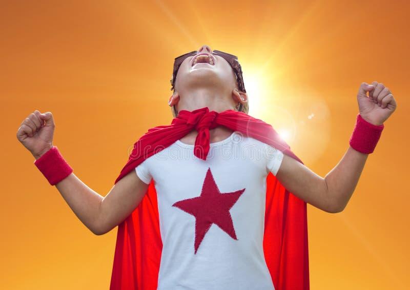Jongen die in superherokostuum tegen oranje achtergrond gillen royalty-vrije stock foto