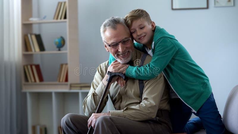 Jongen die teder grootvader, familieliefde, eerbied omhelzen voor oudere generatie stock afbeeldingen