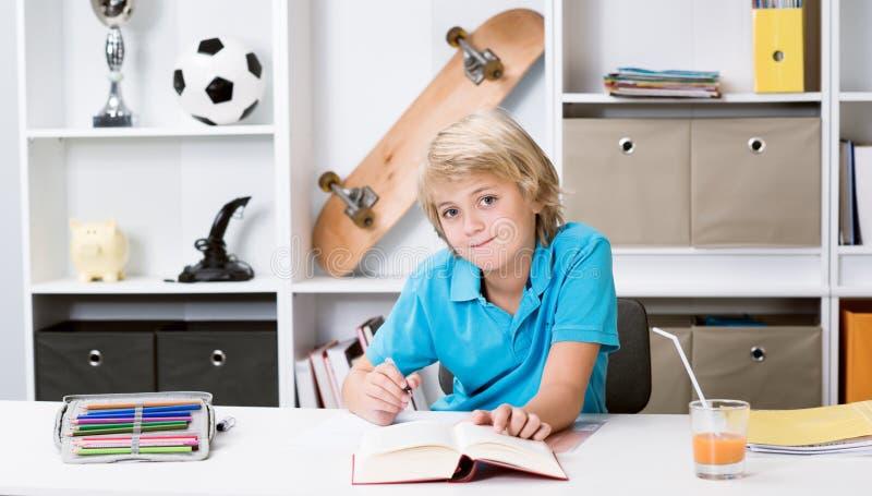 Jongen die thuiswerk doen en een boek lezen royalty-vrije stock foto's