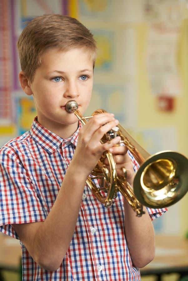 Jongen die Trompet in de Les van de Schoolmuziek leren te spelen stock foto
