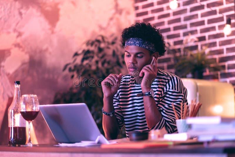 Jongen die van Afrikaanse afdaling aan opnamen van zijn favoriete band door nieuwe hoofdtelefoons luisteren royalty-vrije stock fotografie