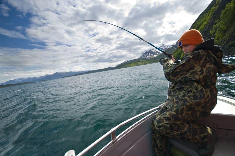 Jongen die van boot vist stock foto's
