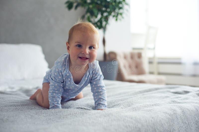 jongen die van de 8 maand de oude gelukkige baby op bed thuis kruipen royalty-vrije stock foto