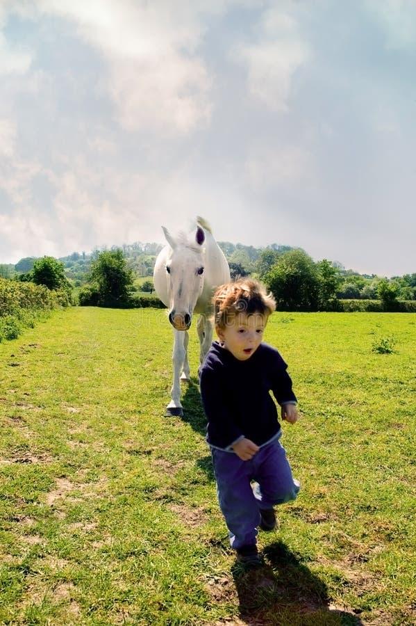 Jongen die van paard loopt. stock afbeeldingen