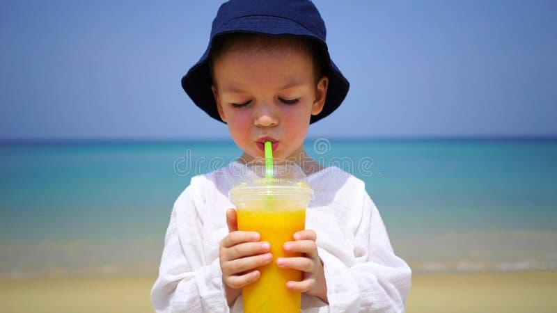 Jongen die van twee jaar mango vers op het strand op de achtergrond van de oceaan drinken royalty-vrije stock afbeeldingen