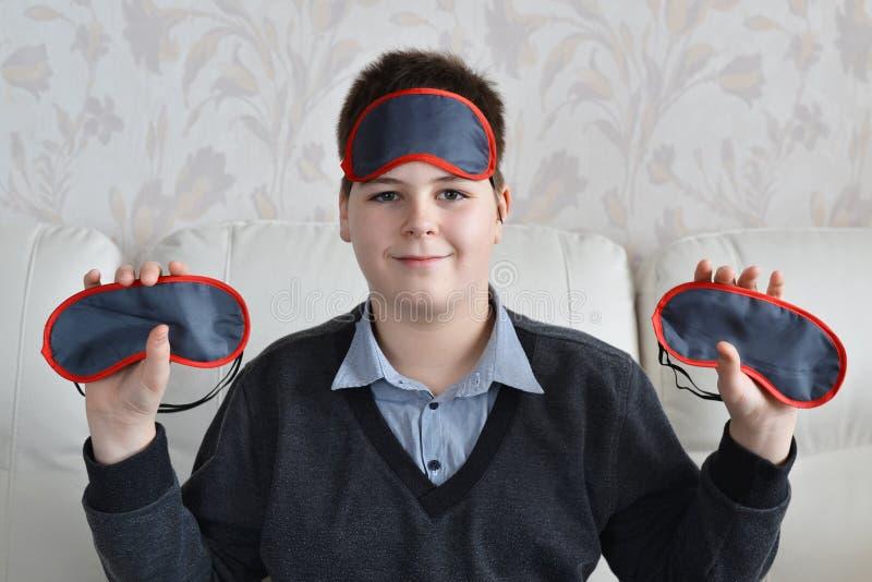 Jongen die verscheidene maskers voor slaap houden stock foto's