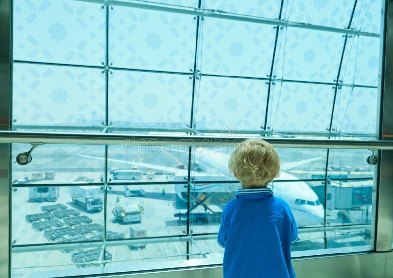 Jongen die vliegtuigen in de luchthaven bekijkt royalty-vrije stock afbeelding