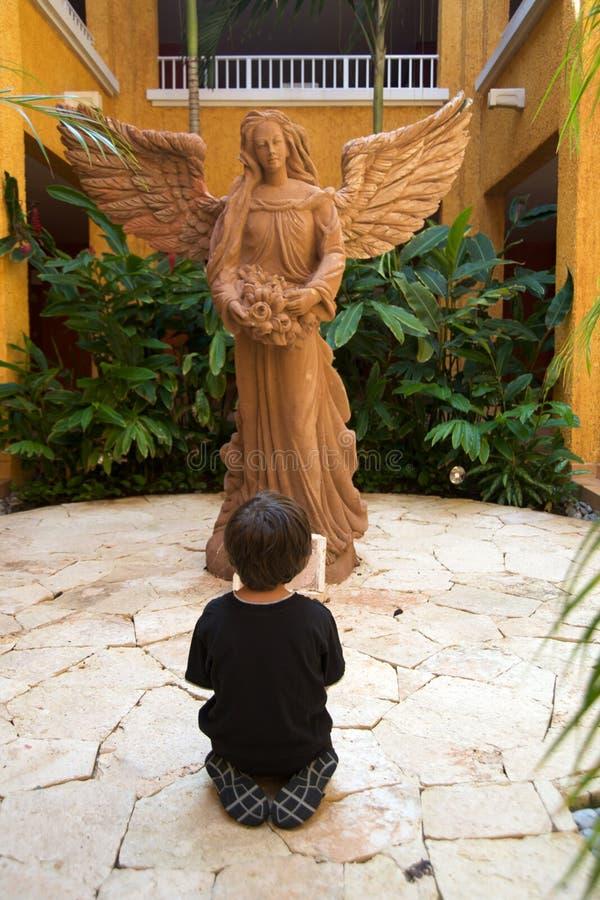 Jongen die voor een engel bidt royalty-vrije stock fotografie