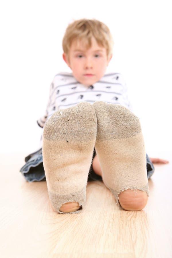 Jongen die vuile sokken met gaten in hen draagt stock afbeeldingen