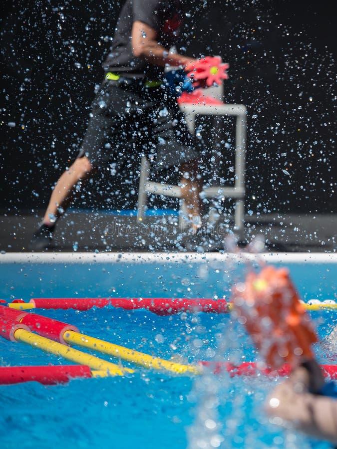 Jongen die water-aërobe's doen met paraplu's in de openlucht in een zwembad royalty-vrije stock afbeelding