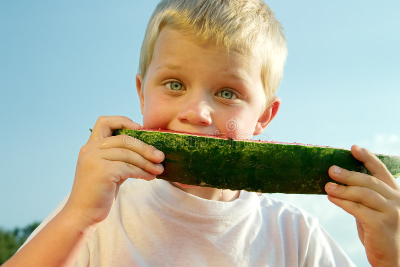 Jongen die watermeloen eet stock afbeeldingen