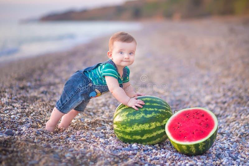 Jongen die watermeloen op het strand eten, zomer die van mooie dag dicht bij oceaan genieten royalty-vrije stock foto