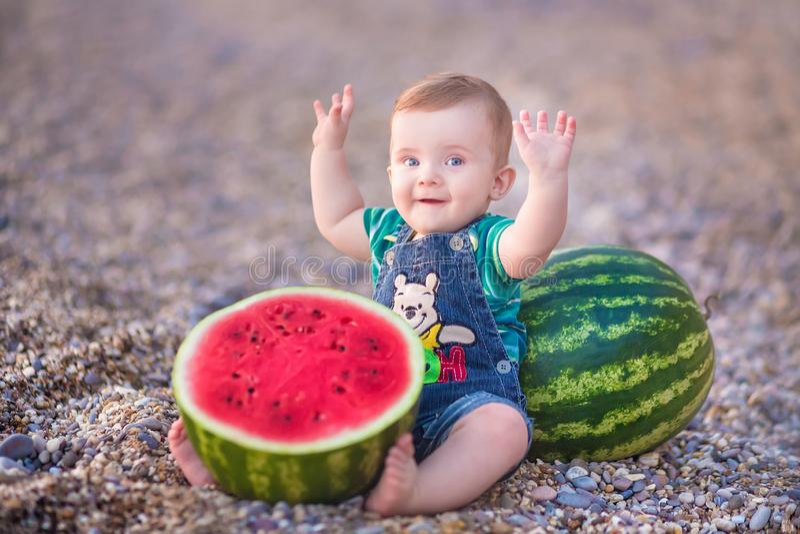 Jongen die watermeloen op het strand eten, zomer die van mooie dag dicht bij oceaan genieten royalty-vrije stock afbeeldingen