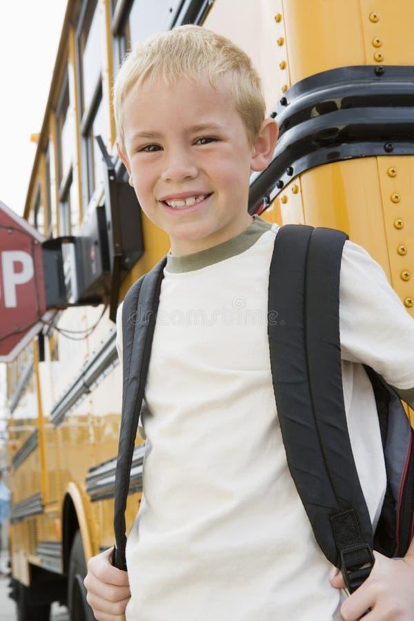Jongen die zich door Schoolbus bevinden stock fotografie