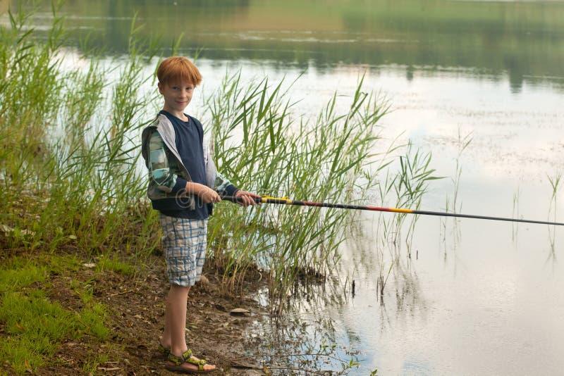 Jongen die zich op een kust en een visserij bevinden royalty-vrije stock afbeeldingen