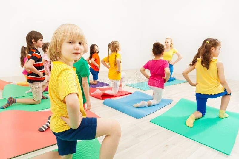 Jongen die zich op knie tijdens gymnastiek- activiteit bevinden royalty-vrije stock foto