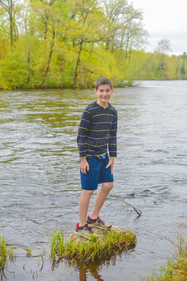 Jongen die zich op Rots in de Rivier van Wisconsin bevinden - Merrill, WI stock afbeeldingen