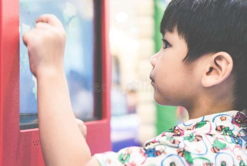 Jongen die zijn hand gebruiken om op de vertoningstechnologie van het aanrakingsscherm te spelen stock fotografie