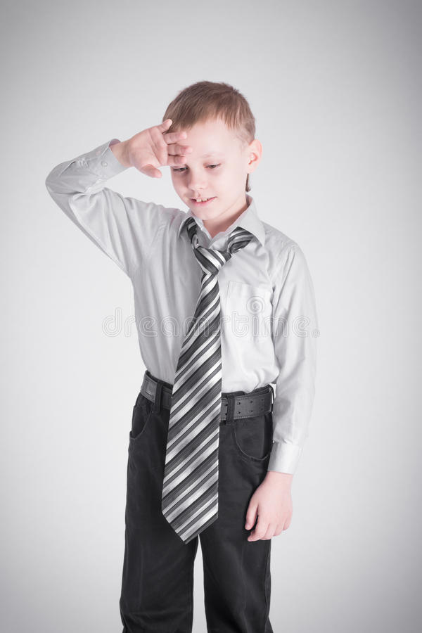 Jongen die zijn hand houden aan zijn voorhoofd stock fotografie