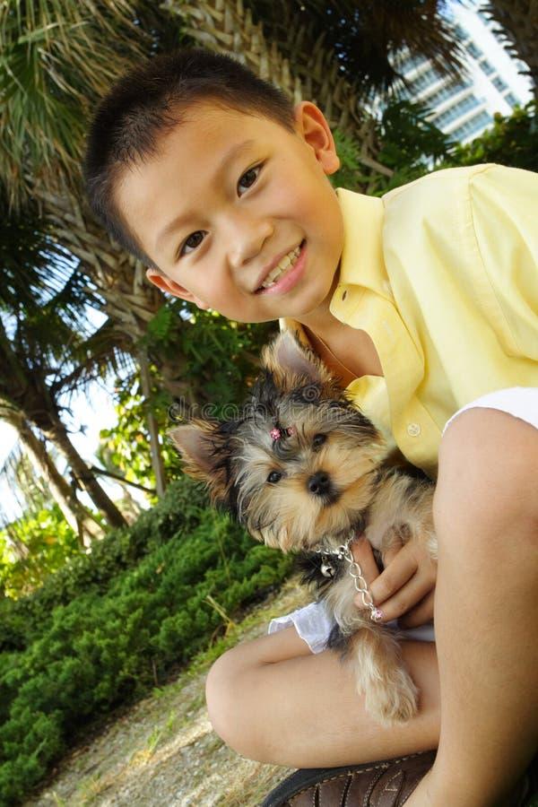 Jongen die zijn puppy houdt stock foto's