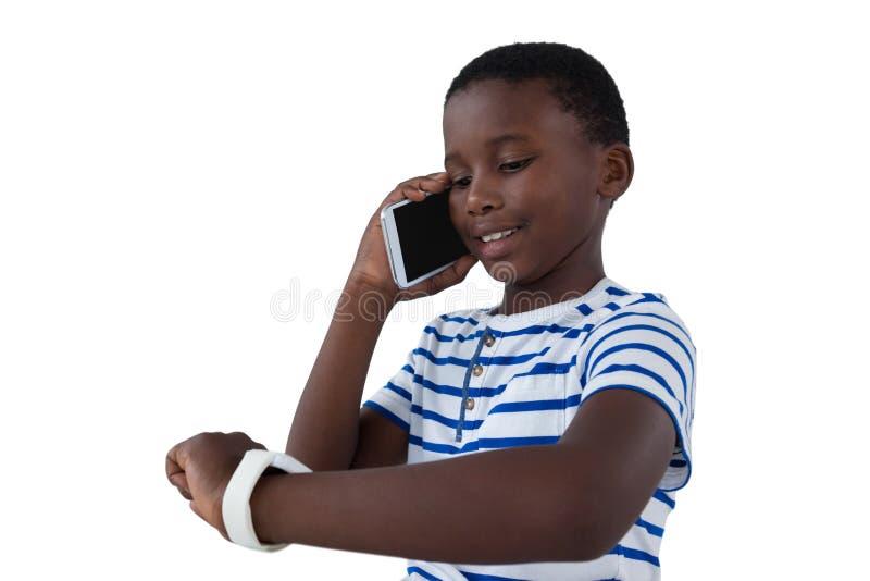 Jongen die zijn slim horloge bekijken terwijl het spreken op mobiele telefoon stock foto