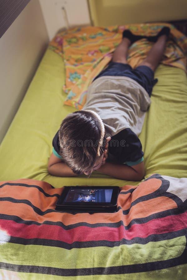Jongen die zijn tablet kijken stock foto's