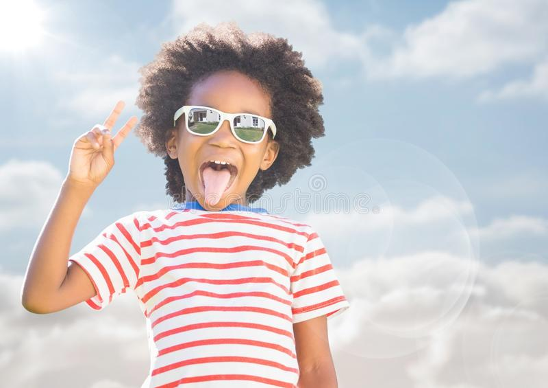 Jongen die in zonnebril vredesteken maken tegen hemel met gloed royalty-vrije stock fotografie