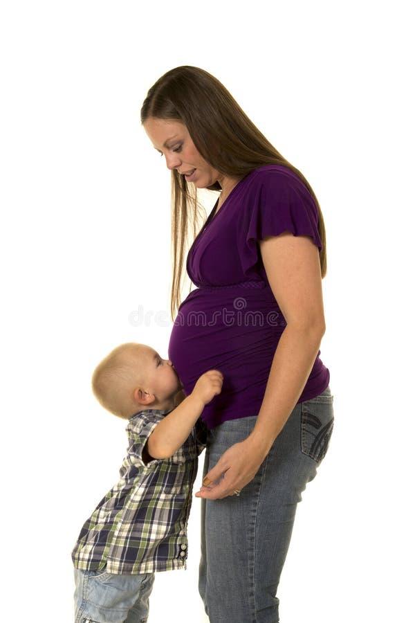 Jongen die zwangere buik van mamma in purper overhemd kussen royalty-vrije stock foto