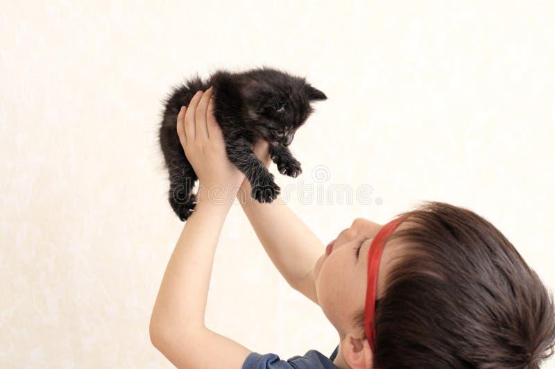 Jongen die zwart katje steunen royalty-vrije stock foto
