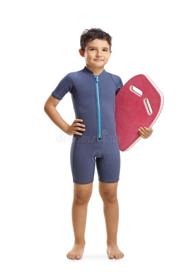Jongen in een wetsuit die een zwemmende vlotterraad houden royalty-vrije stock foto's
