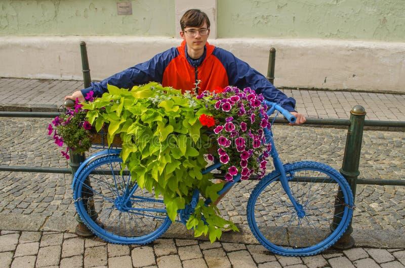 Jongen en bloemen bed op een oude fiets