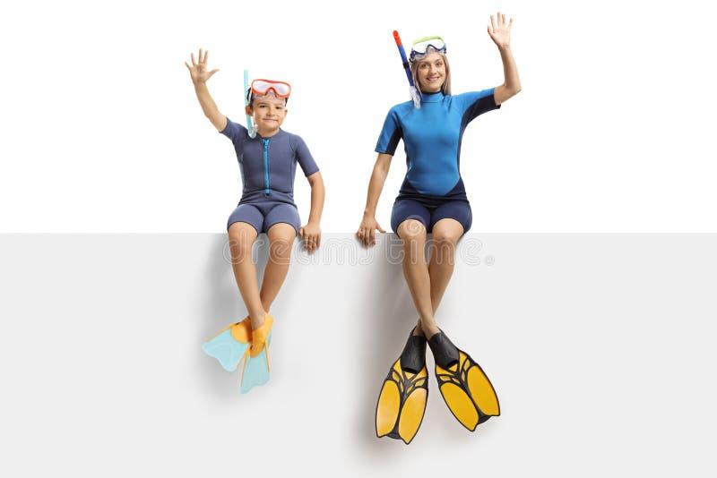 Jongen en een vrouw op een paneel die en een wetsuit, een het duiken masker en het duiken vinnen golven dragen royalty-vrije stock foto's