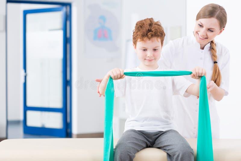 Jongen en fysieke therapie in kliniek stock afbeeldingen