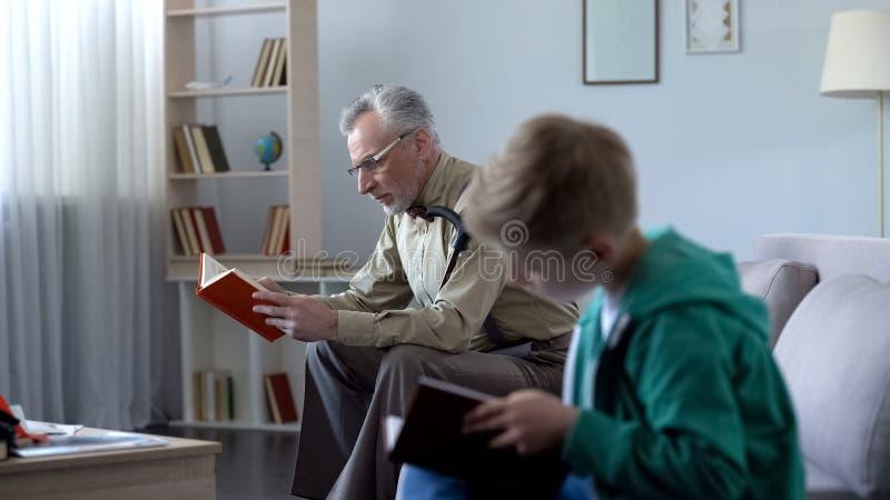 Jongen en grootvaderlezingsboeken, concept onderwijs beschikbaar op om het even welke tijd royalty-vrije stock afbeeldingen