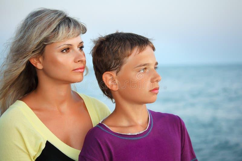 Jongen en jonge vrouw op strand in avond stock fotografie