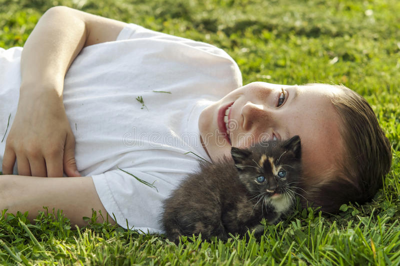 Jongen en katje samen op gras royalty-vrije stock foto's